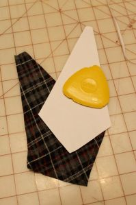 Cut out a good shaped tie, then used a chalk triangle (pictured) to trace it onto some fabric.  Cut.